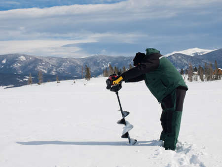 Fisherman eith an auger on the frozen lake Granby, Colorado. photo