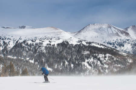 loveland: Single skier fighting strong winter wind. Stock Photo