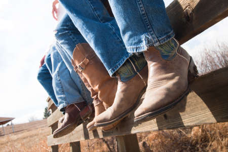 fence: Cowboys and cowgirls sitting on wooden fence.