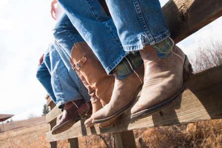 Cowboys en de Veedrijfsters zittend op houten hek.