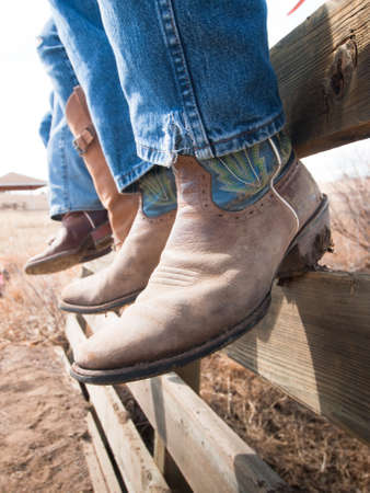 botas vaqueras: Cowboys y cowgirls sentado en la valla de madera.
