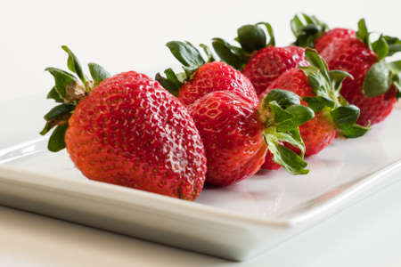 Fresh ripe strawberries on long white plate. photo