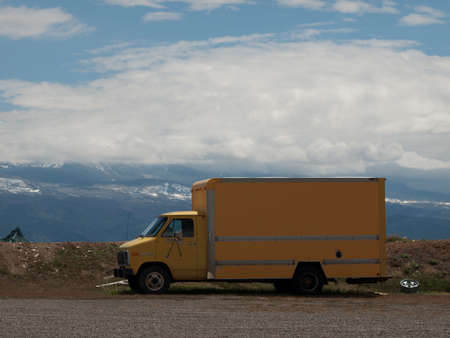 Yellow moving truck on the dirt road. Stock Photo - 9639986