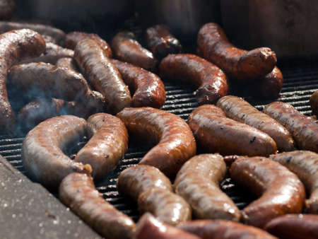 Many bratwursts on the grill at festival photo