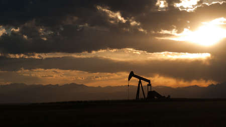 field sunset: A pumpjack silhoutte with dramatic sunset.
