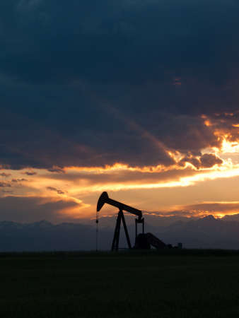Un silhoutte de pumpjack avec le coucher de soleil spectaculaire.