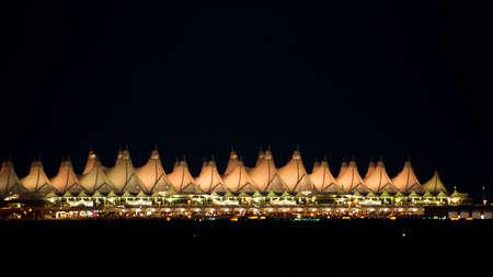 Denver International Airport at night against dark sky.