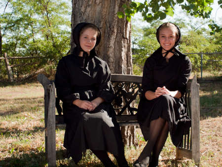 Two amish girls on the bench. Stock Photo - 10354726