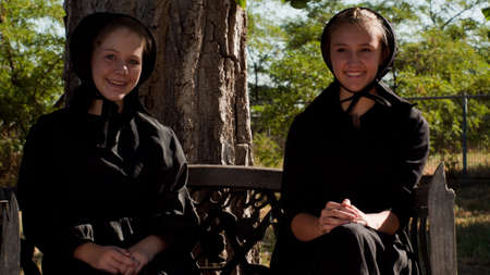 Two amish girls on the bench. Stock Photo - 10354716