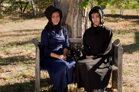 Two amish girls on the bench. Stock Photo - 10354725