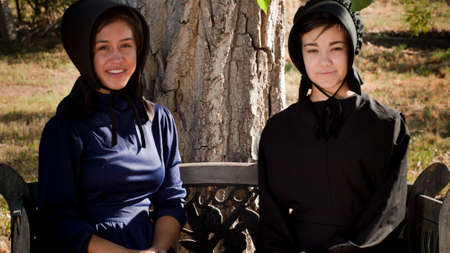 Two amish girls on the bench.