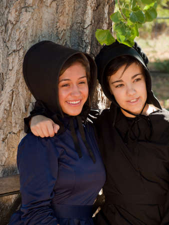 religious clothing: Two amish girls on the bench. Editorial