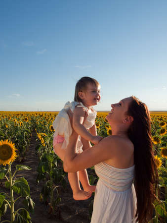 Mother and daughter playing in sunflower field. Stock Photo - 10378021