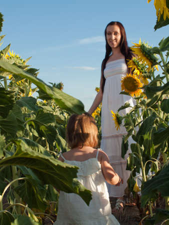Mother and daughter playing in sunflower field. Stock Photo - 10378035