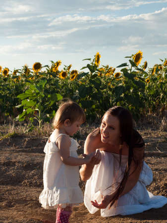 Mother and daughter playing in sunflower field. photo