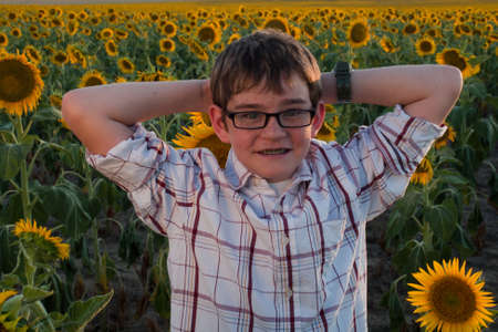 Boy in plaid shirt and glasses at sunflower field. Stock Photo - 10378094