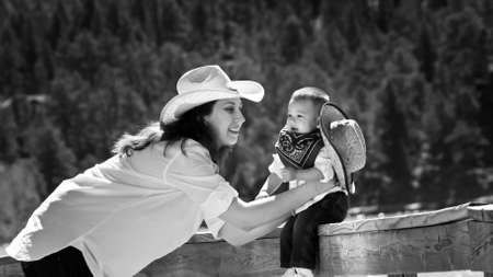 Young mother with her son dressed up in cowboy clothes. photo