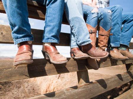 Cowboys en cowgirls zittend op een houten hek.