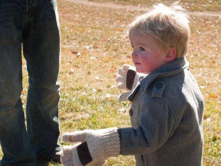 oversize: Toddler trying oversize gloves.