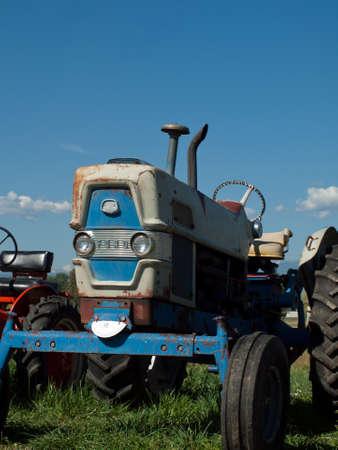 Men harvesting hay with old farm equipment.
