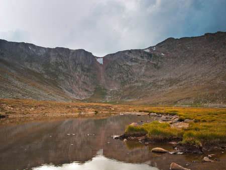 Beautiful Summit Lake reflects towering Mt. Evans and is surrounded by lush vegetation. Colorado. Stock Photo - 10633845