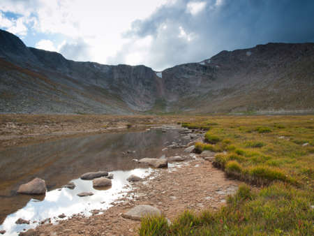 mount evans: Beautiful Summit Lake reflects towering Mt. Evans and is surrounded by lush vegetation. Colorado.