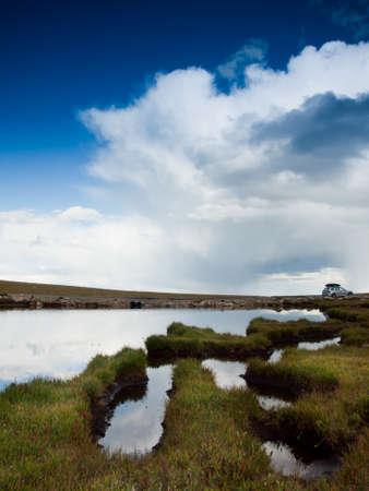 Beautiful Summit Lake reflects towering Mt. Evans and is surrounded by lush vegetation. Colorado. Stock Photo - 10633789