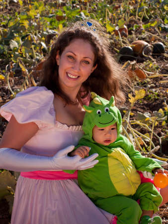 Toddler and his mother dressed up in cute costumes at the pumpkin patch. photo