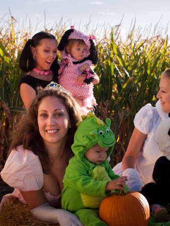 Toddlers and their mothers dressed up in cute costumes at the pumpkin patch. photo