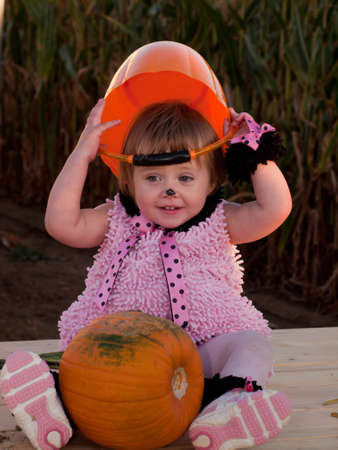 Toddler dressed up in cute costumes at the pumpkin patch. Stock Photo - 10806594