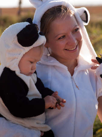 Toddler and her mother dressed up in cute costumes at the pumpkin patch.