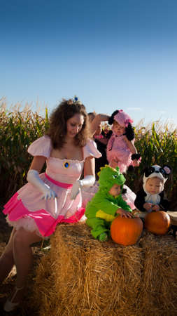 Toddlers and their mothers dressed up in cute costumes at the pumpkin patch.