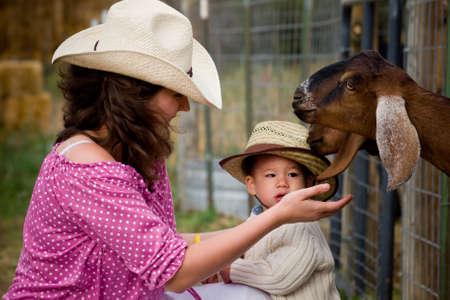 Jongen peuter met zijn moeder op de boerderij.