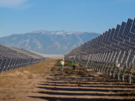 A series of large solar panels forms a symmetrical line at a power plant in the San Luis Valley of central Colorado. These panels utilize a tracking system to follow the sun, collecting its energy and using photovoltaic cells to transform the sunlight int