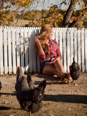 old people: Country girl surrownded by chickens. Stock Photo