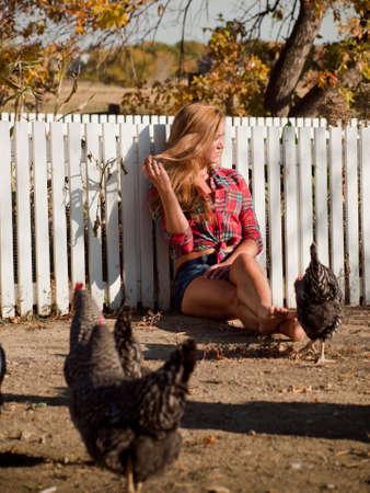 Land meisje surrownded door kippen. Stockfoto
