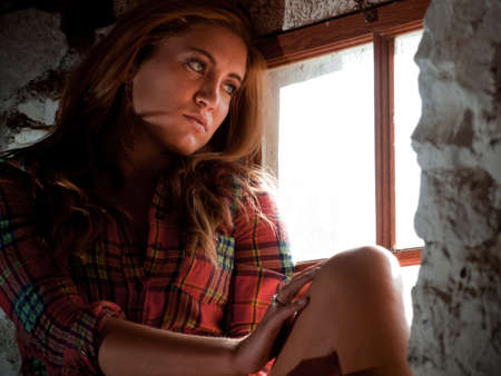 window seal: Country girl inside of an old barn. Stock Photo
