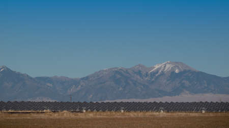 Una serie de grandes paneles solares forman una línea simétrica en una central eléctrica en el Valle de San Luis de Colorado central. Estos paneles utilizan un sistema de seguimiento para seguir el sol, recogiendo su energía y el uso de células fotovoltaicas para convertir la luz solar int Foto de archivo - 11078912