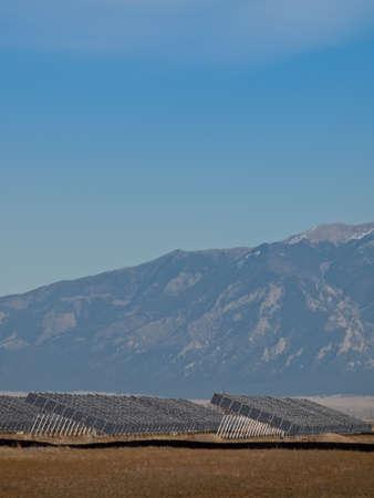 Una serie de grandes paneles solares forman una l?nea sim?trica en una central el?ctrica en el Valle de San Luis de Colorado central. Estos paneles utilizan un sistema de seguimiento para seguir el sol, recogiendo su energ?a y el uso de c?lulas fotovoltaicas para convertir la luz solar int Foto de archivo - 11092025