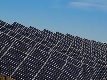 Una serie de grandes paneles solares forman una línea simétrica en una central eléctrica en el Valle de San Luis de Colorado central. Estos paneles utilizan un sistema de seguimiento para seguir el sol, recogiendo su energía y el uso de células fotovoltaicas para convertir la luz solar int Foto de archivo - 11092073