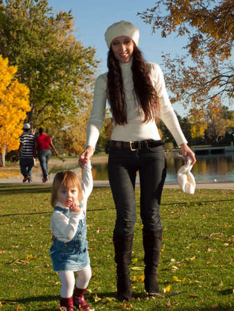 women jeans: Girl toddler with her mother in autumn park.