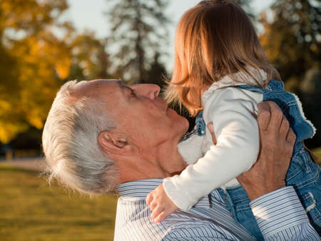 grandaughter: Girl toddler with grandfather in autumn park. Stock Photo