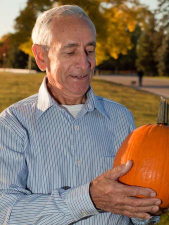 Happy elderly man with pumpkins. Stock Photo - 11150167