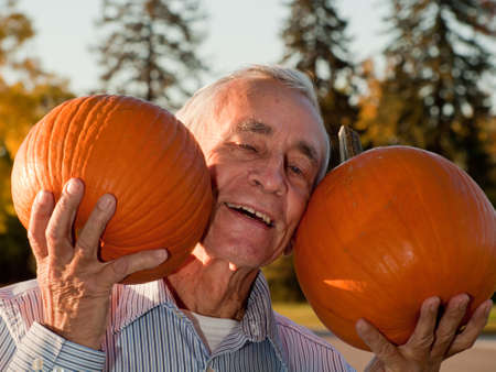 Happy elderly man with pumpkins. Stock Photo - 11130646