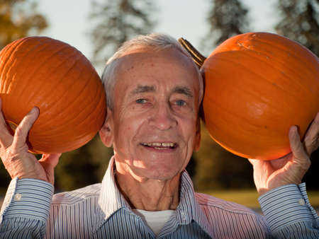 Happy elderly man with pumpkins. photo