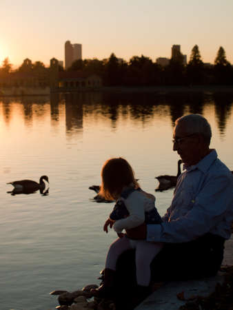 grandaughter: Girl toddler with grandfather by lake at sunset. Stock Photo