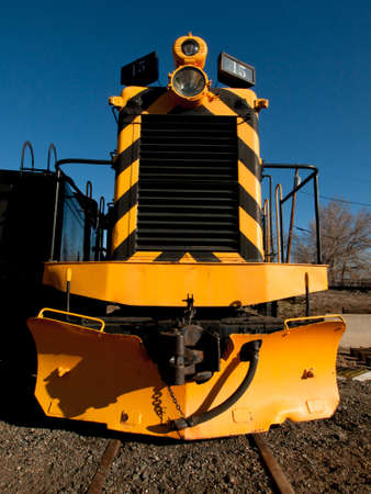 Vintage yellow locomotive at front of the roundhouse.