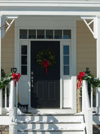 front of: House decorated for winter holidays.