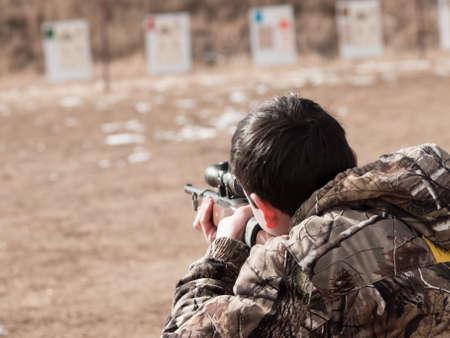 사격: 어린 소년 애플 시드 프로젝트에서 소총 사격 연습. 스톡 사진