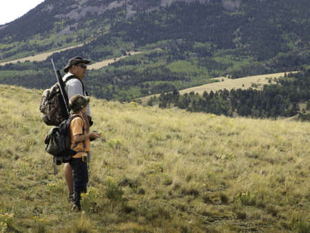 hunting rifle: A father and scouting area for big game hunt. Image taken in Colorado. Stock Photo